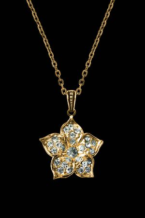 Gold flower pendant with crystals hanging on a chain on black background