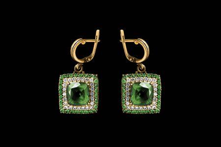 Elegant emerald gold earrings with diamonds on black background