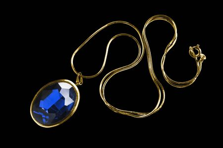 Large blue sapphire pendant on gold chain isolated over black