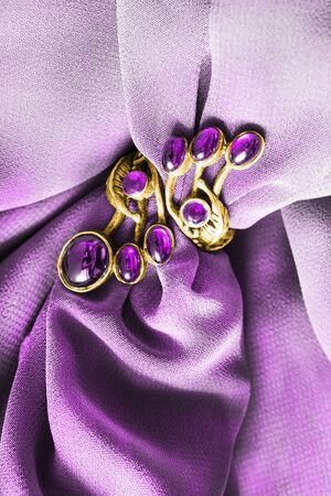 Vintage gold amethyst ring on draped purple textile background closeup