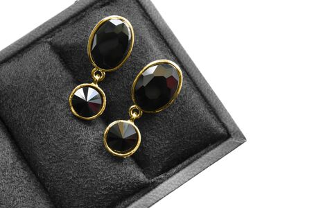 Elegant black onyx gold earrings in jewel box on white background