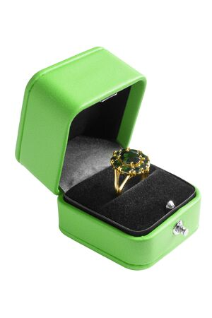 Gold emerald ring in opened jewel box isolated over white