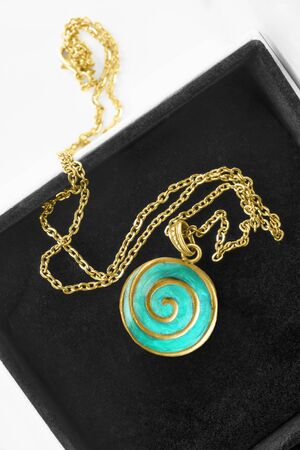 Vintage gold necklace with turquoise locket in black jewel box closeup