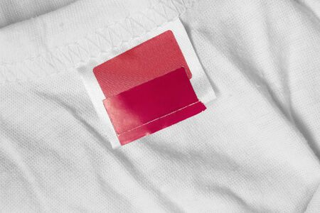 Blank red clothes label on white cotton background