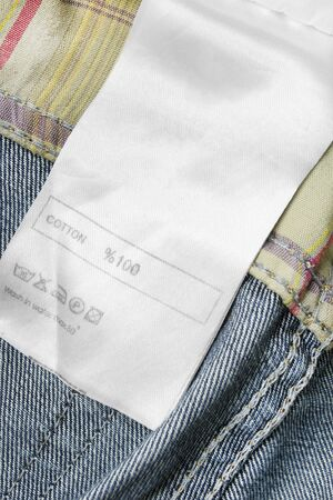 Fabric composition and care clothes label on textile background closeup