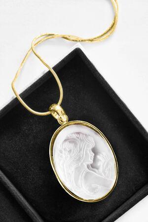 Elegant vintage gold necklace whti white cameo locket in black jewel box Stockfoto