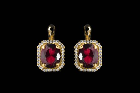 Luxury gold ruby earrings with diamonds on black background