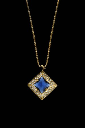 Gold blue gem pendant with diamonds hanging on a chain isolated over black