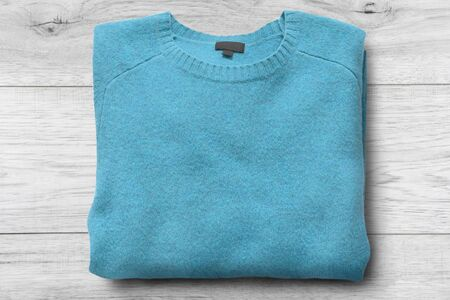 Folded blue cashmere sweater on white wooden background