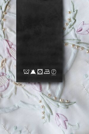 Black care clothes label on embroidered silk background closeup