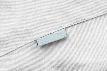 Blank blue clothes label on white textile background