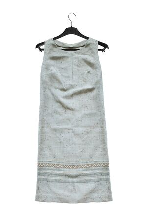 Linen ethnic sleeveless dress hanging on black clothes rack isolated over white
