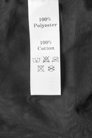 Fabric composition and care clothing label on black textile background