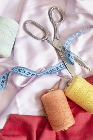 Scissors and sewing items on colorful textile background Banco de Imagens