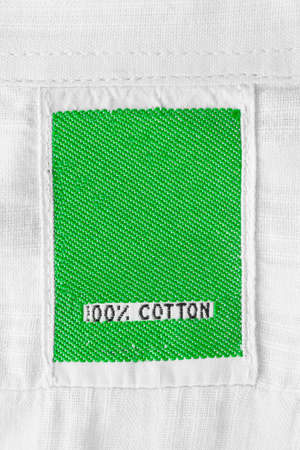 Green clothing label says 100% cotton on white textile background 스톡 콘텐츠