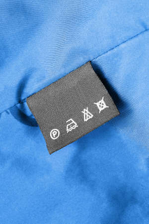 Washing instructions clothes label on blue silk as a background Stockfoto