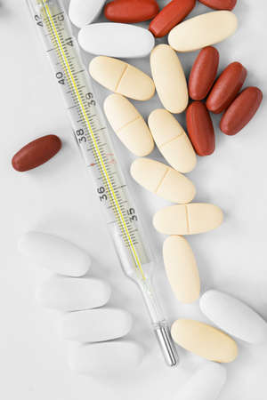 Thermometer and lot of medical pills closeup on white background