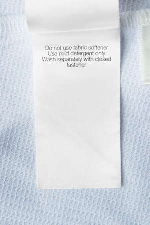 Care clothing label on blue textile background closeup Stockfoto