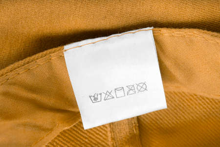 Care clothing label on yellow textile background Stockfoto