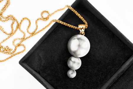 Elegant white pearls gold necklace in black jewel box closeup