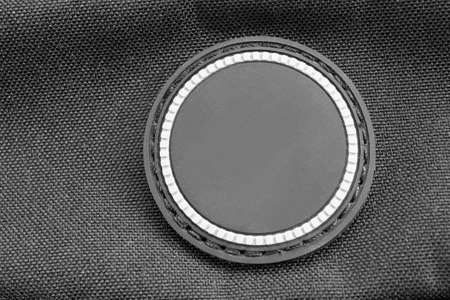 Blank rubber patch on black textile background closeup