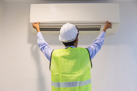 specialist cleans and repairs the wall air conditioner Stock Photo