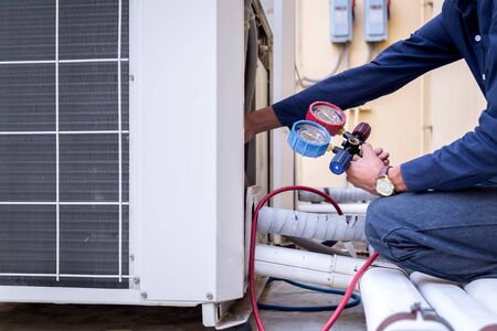 Technician is checking air conditioner ,measuring equipment for filling air conditioners.