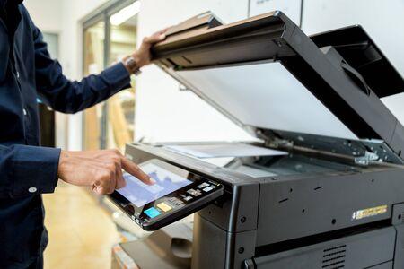 Bussiness man Hand press button on panel of printer, printer scanner laser office copy machine supplies start concept. Imagens
