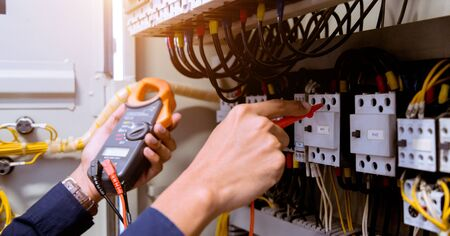 Electrician measurements with multimeter testing current electric in control panel. Standard-Bild