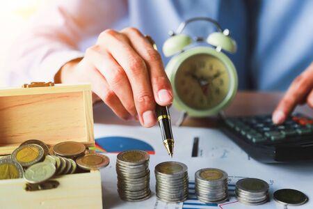 Close up,Hand putting money coins stack in saving money and growing business concept. 写真素材