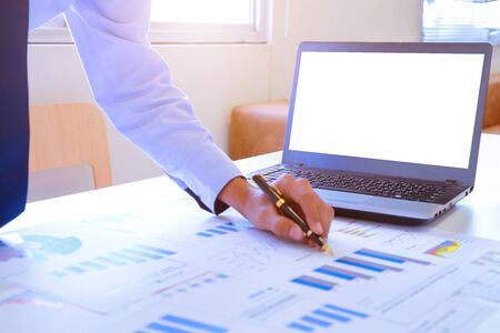Young businessman holding pen pointing to graph and chart in the office. Accounting and finance Concept. Фото со стока