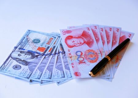 100 Yuan China currency banknotes and 100 US Dollar banknotes on a pile of international currencies banknotes.