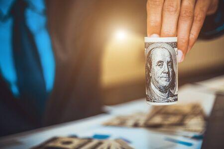 Businessman's hands holding money dollar.