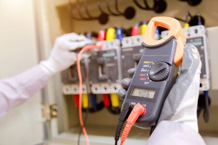 Technician is measuring voltage or current by voltmeter in control panel of power plan with checklist System ready.