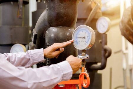 Engineer checking Condenser Water pump and pressure gauge , chiller water pump with pressure gauge.System ready. 免版税图像