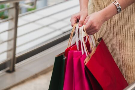 Closeup of woman holding shopping bags on the street with copy space.