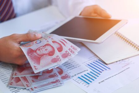 Businessman with money in hand, Yuan,investment, success and profitable business concepts.