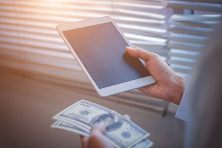 Businessman with cash dollars - business concept,tablet and finance,investment,save,success and profitable business concepts.