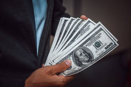 Close up, of male hands counting dollar bills, filtered image, business man working financial adviser and counting money banknotes