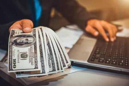 Businessman with cash dollars - business concept,computer and finance,investment,save.