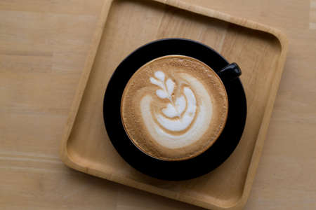 Cup of coffee latte on wooden background. Top view.