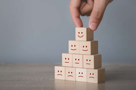 Customer pressing smiley face emoticon on wood cube, Service rating, satisfaction concept. 免版税图像