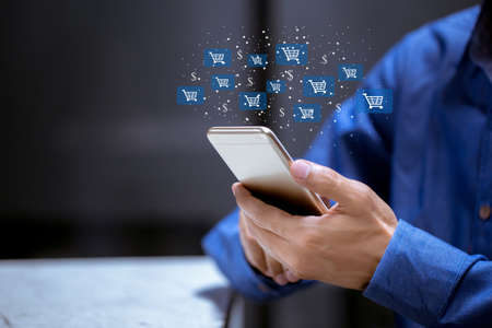 Business using smartphone,with shopping cart icon,sale volume increase make business growth and shopping online concept. 免版税图像