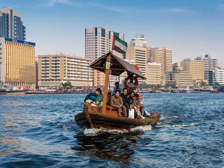 bur dubai: DUBAI, UNITED ARAB EMIRATES UAE - JANUARY 26, 2014: People crossing the Creek from Deira to Bur by abra, a traditional wooden water taxi in Dubai, United Arab Emirates