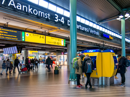 SCHIPHOL AMSTERDAM AIRPORT, NETHERLANDS - JANUARY 15, 2015: Tourists and travellers at Schiphol Amsterdam Airport train terminal, Netherlands