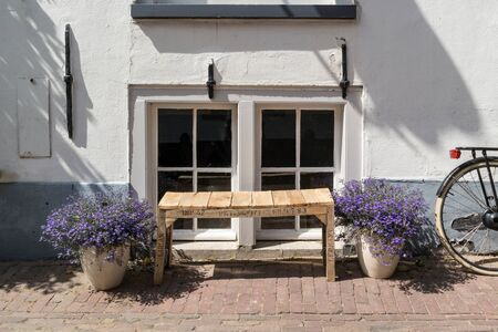 wheel house: Dutch city street scene with selfmade wooden bench, flowers in pots and wheel of bicycle in front of windows of old house in Amersfoort in province of Utrecht, Netherlands