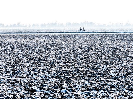 bicyclists: Silhouette of two bicyclists in winter polder landscape near Zevenhuizen in the province of South Holland, Netherlands