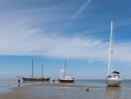 WADDENSEA, NETHERLANDS - MAY 31, 2014: Sailboats at ebb tide on the tidal flats wetlands of the Waddensea north of the Netherlands