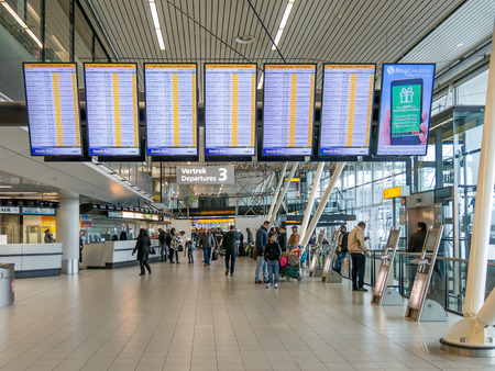AMSTERDAM SCHIPHOL AIRPORT, NETHERLANDS - JAN 25, 2015: Flight departures boards and passengers in departure terminal of Schiphol Amsterdam Airport, Netherlands