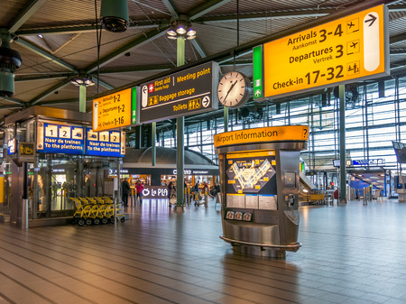 schiphol: AMSTERDAM SCHIPHOL AIRPORT, NETHERLANDS - JAN 25, 2015: Information and direction signs in train station terminal of Schiphol Amsterdam Airport, Netherlands